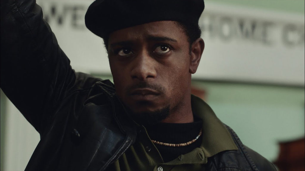 Screenshot from Judas and the Black Messiah; Lakeith Stanfield holding up a revolutionary fist while portraying Bill O'Neal at a Black Panther rally.